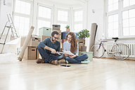 Couple surrounded by cardboard boxes sitting on floor - RBF004724
