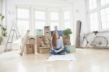 Woman surrounded by cardboard boxes sitting on floor with construction plan - RBF004727