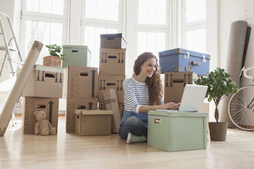 Woman surrounded by cardboard boxes using laptop - RBF004736