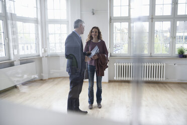 Real estate agent talking to client in empty apartment - RBF004739