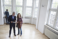 Real estate agent talking to client in empty apartment - RBF004742
