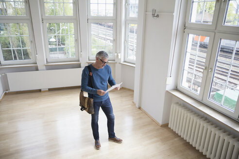 Man looking at document in empty apartment - RBF004745