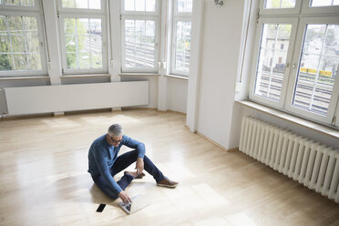 Man using laptop in empty apartment - RBF004751