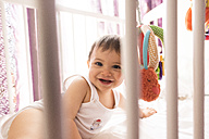 Portrait of happy baby boy in his cot - JASF000980
