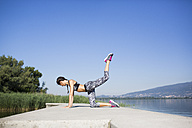 Young woman doing exercise on pier, lifting leg - MRAF000077