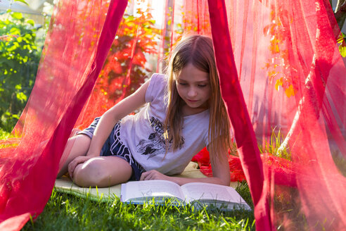 Girl sitting on a meadow under mosquito net reading a book - SARF002811