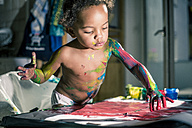 Girl draws red picture with fingercolors and is fully smeared of colors - YNF000025