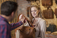 Shop assistant showing leather bag to woman - ZEF008925