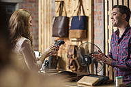 Woman paying with credit card in leather goods shop - ZEF008931