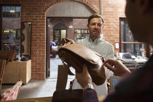 Man handing over leather bag in shop - ZEF008937