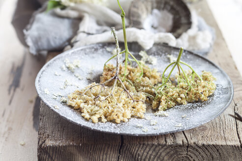 Baked elder flowers with icing sugar on plate - SBDF003015