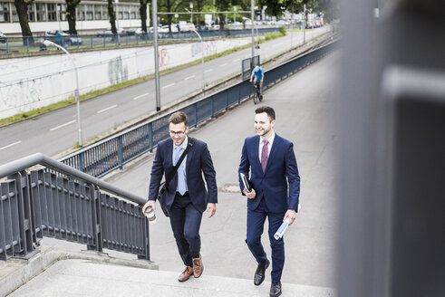 Two young businessmen walking together in the city - UUF007974