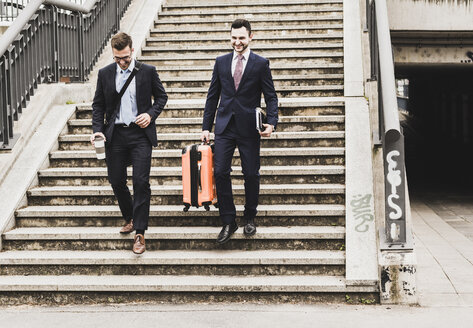 Businessmen on business trip walking down stairs with wheeled luggage - UUF007989