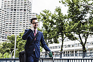 Businessman with bicycle walking in the city, using smart phone - UUF007995