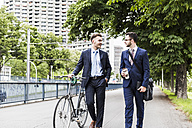 Businessmen walking with bicycle in the city, talking - UUF008001