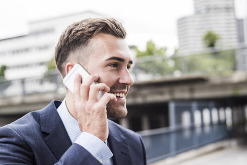 Portrait of a young businessman talking on the phone - UUF008007