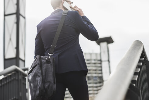 Young businessman standing at railing, using smart phone - UUF008010
