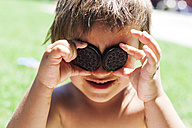 Little boy covering his eyes with chocolate cookies - VABF000659