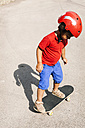 Little boy with red safety helmet standing on skateboard - VABF000668
