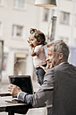Businessman with little daughter working on laptop in cafe - KNSF000009