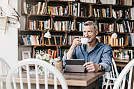 Mature man sitting in cafe with digital tablet, drinking coffee - KNSF000042