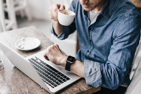 Mature man drinking coffee while working at laptop, looking at smartwatch - KNSF000045
