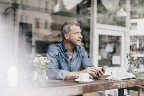 Mature man sitting in cafe - KNSF000051