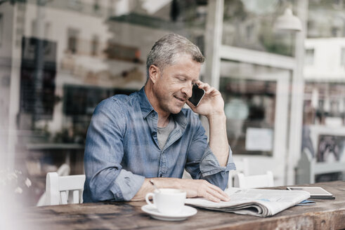 Mature man sitting in cafe talking on the phone - KNSF000054