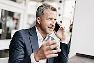 Businessman in cafe using smart phone - KNSF000063