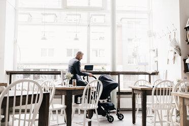 Businessman sitting in cafe with pram - KNSF000069