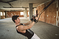Young man exercising suspension training trx - RAEF001261