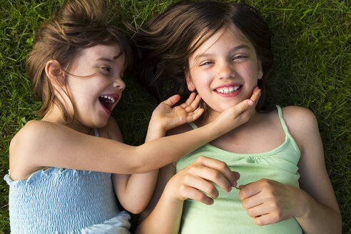 Two sisters lying in meadow having fun - LVF005113
