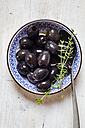 Black olives in bowl with thyme - SBDF003033