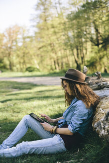 Woman sitting on a meadow using digital tablet - AKNF000047