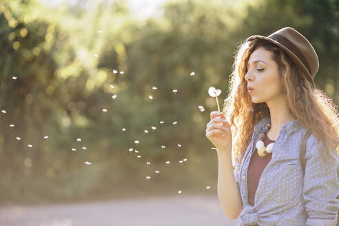 Young woman blowing dandelion - AKNF000059