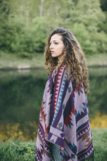 Portrait of young woman wearing patterned poncho - AKNF000062