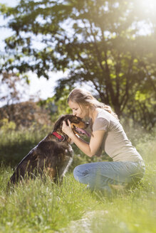 Young woman kissing her mongrel on a meadow - MIDF000749