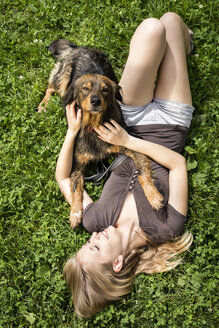 Young woman relaxing with her dog on a meadow - MIDF000758