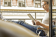 Man sitting on balcony using digital tablet - FMKF002751