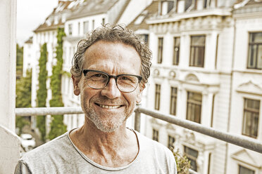 Portrait of happy man wearing glasses on his balcony - FMKF002754