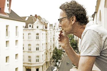 Man smoking on balcony - FMKF002760