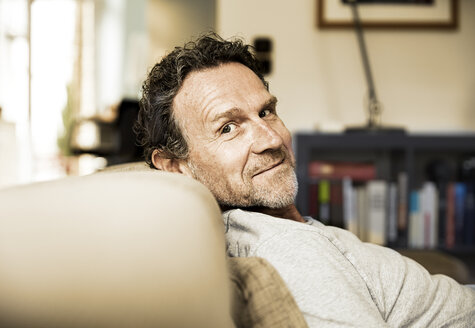 Portrait of smiling man with stubble relaxing on the couch - FMKF002766
