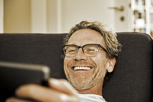 Portrait of laughing man lying on the couch using tablet - FMKF002772