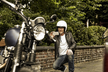 Smiling man with motorcycle helmet taking photo of his motorbike - FMKF002775