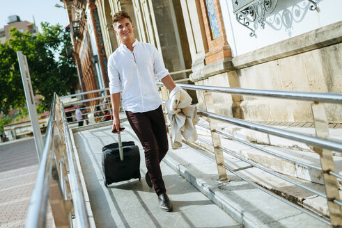 Young man leaving station with suitcase - KIJF000528