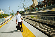 Young man with suitcase walking at station platform - KIJF000537