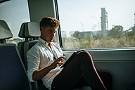 Young man using a tablet on a train - KIJF000543