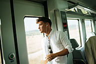Young man looking out the door on a train - KIJF000549