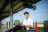 Young man using a laptop at station platform - KIJF000555