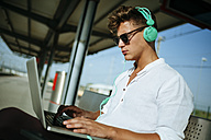 Young man wearing headphones and using a laptop at station platform - KIJF000558